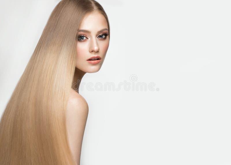 有一根完全光滑的头发的美丽的白肤金发的女孩和经典构成 秀丽表面 库存图片