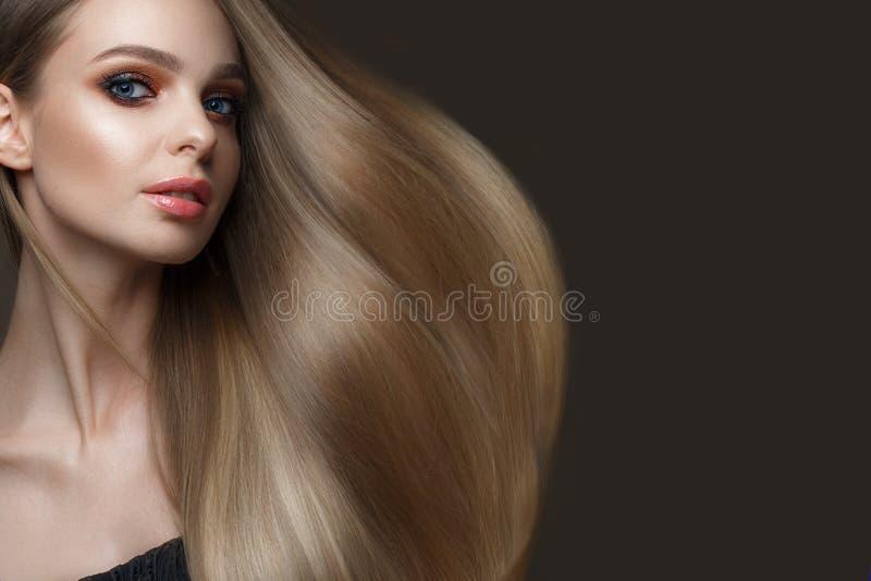 有一根完全光滑的头发的美丽的白肤金发的女孩,经典构成 秀丽表面 免版税库存图片