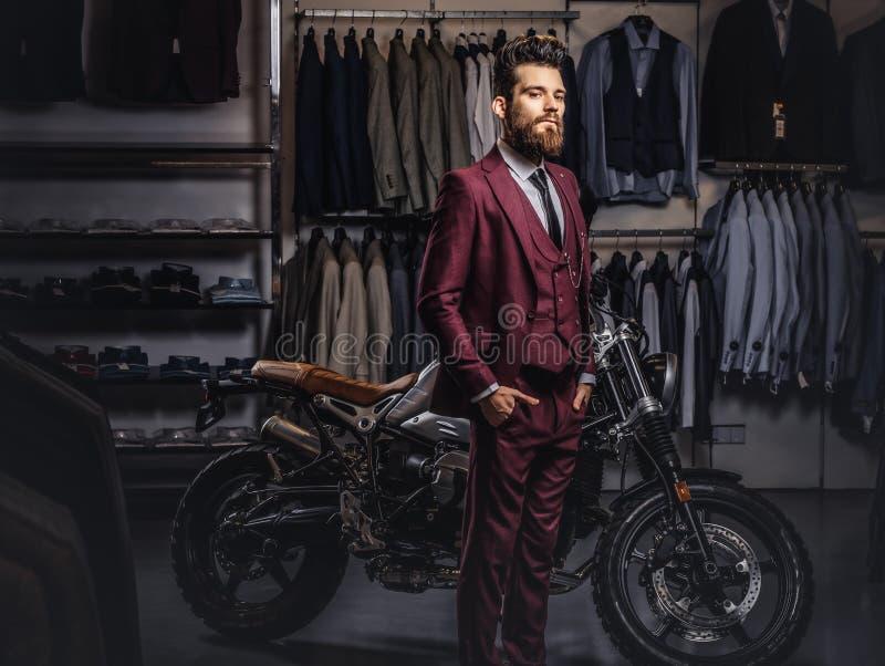 有一根时髦的胡子和头发的英俊的人在摆在减速火箭的体育摩托车附近的葡萄酒红色衣服穿戴了在人` s 库存照片