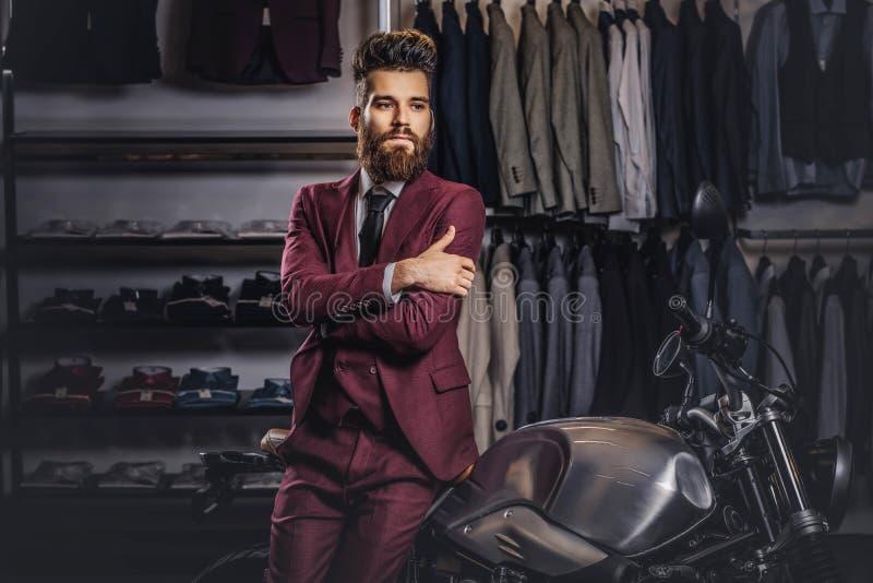 有一根时髦的胡子和头发的英俊的人在摆在减速火箭的体育摩托车附近的葡萄酒红色衣服穿戴了在人` s 图库摄影