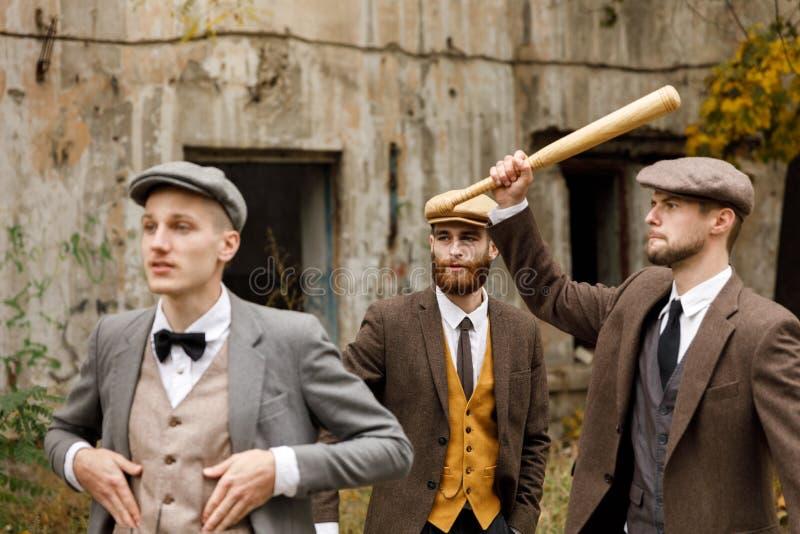 有一根棒的三位匪徒在一个被放弃的大厦附近 减速火箭 户外 免版税库存图片