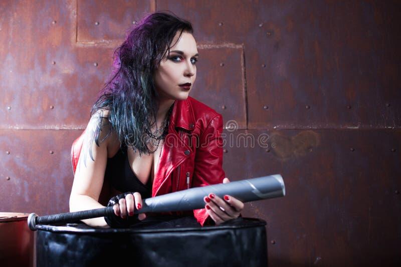 有一根棒的积极的低劣的妇女,在红色皮夹克 免版税库存图片