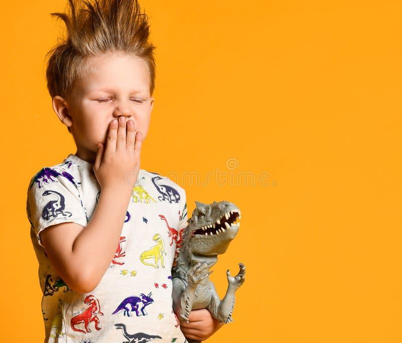 有一根滑稽,被弄乱的头发的小男孩拿着玩具塑料恐龙作为画象 库存照片