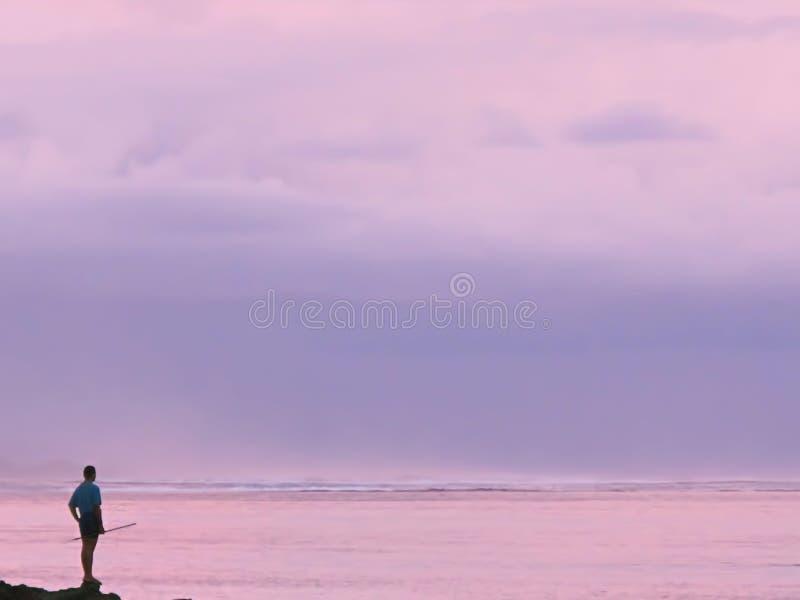 有一根钓鱼竿的人在与海波浪的桃红色日落前面 免版税库存照片