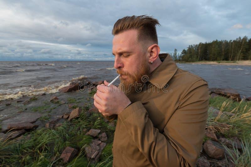 有一根香烟的有胡子的人在多暴风雨的天气的海滨 免版税库存图片