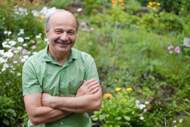有一根髭和一个秃头斑点的一个年长人在一件绿色T恤杉在花在夏天庭院里,胳膊中站立 免版税库存图片