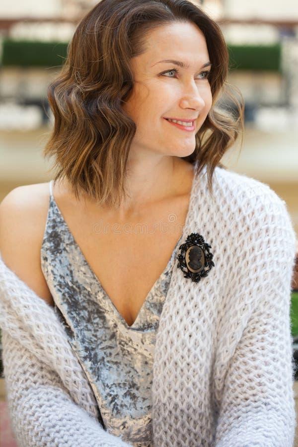 有一根黑有浮雕的贝壳别针的微笑的美丽的妇女 免版税库存照片