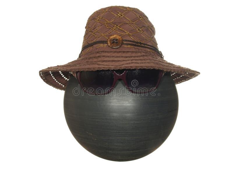 有一根黑鞋带的夫人的棕色帽子和在白色背景隔绝的一个黑塑料球的按钮和黑暗的风镜 免版税库存照片