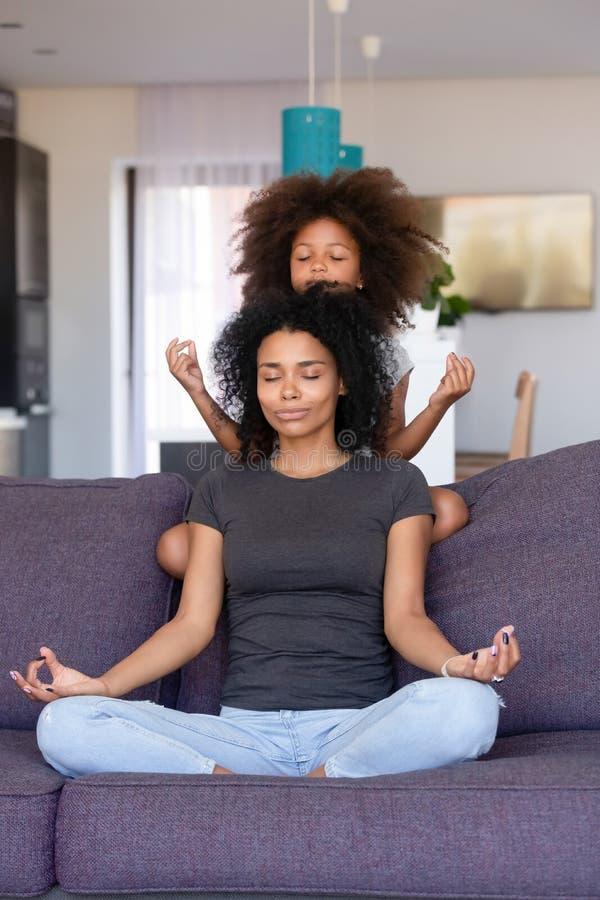 有一点女儿实践的瑜伽的非裔美国人的妇女在家 免版税库存图片