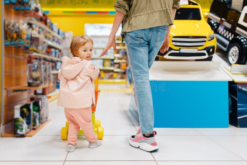 有一点女儿的愉快的母亲在孩子商店 免版税图库摄影