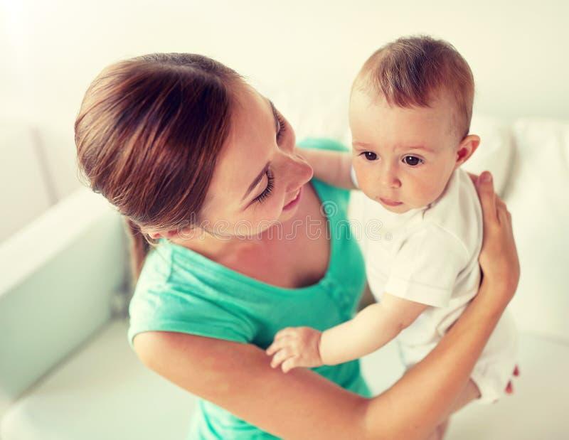 有一点婴孩的愉快的年轻母亲在家 免版税库存照片