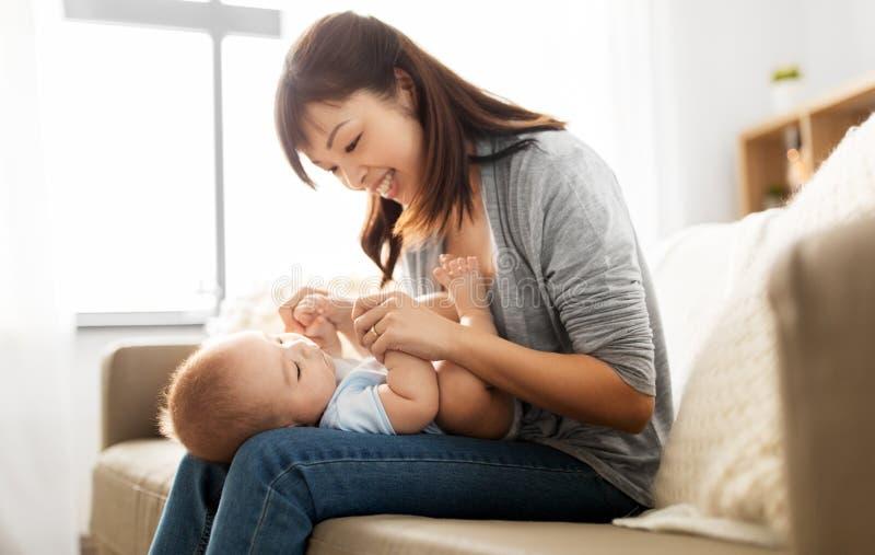 有一点小儿子的愉快的年轻母亲在家 库存图片