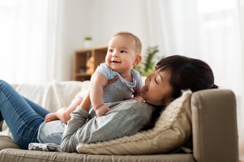 有一点小儿子的愉快的母亲在家 免版税库存图片