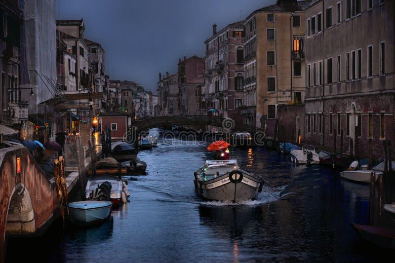 有一点小船的小运河有有红色伞的人和行的老房子的在黄昏在下雨天在威尼斯,意大利 免版税库存图片