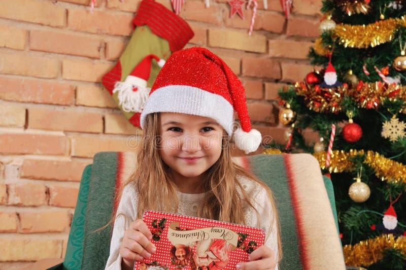 有一点红色箱子的女婴在椅子的手上在圣诞树附近 库存图片