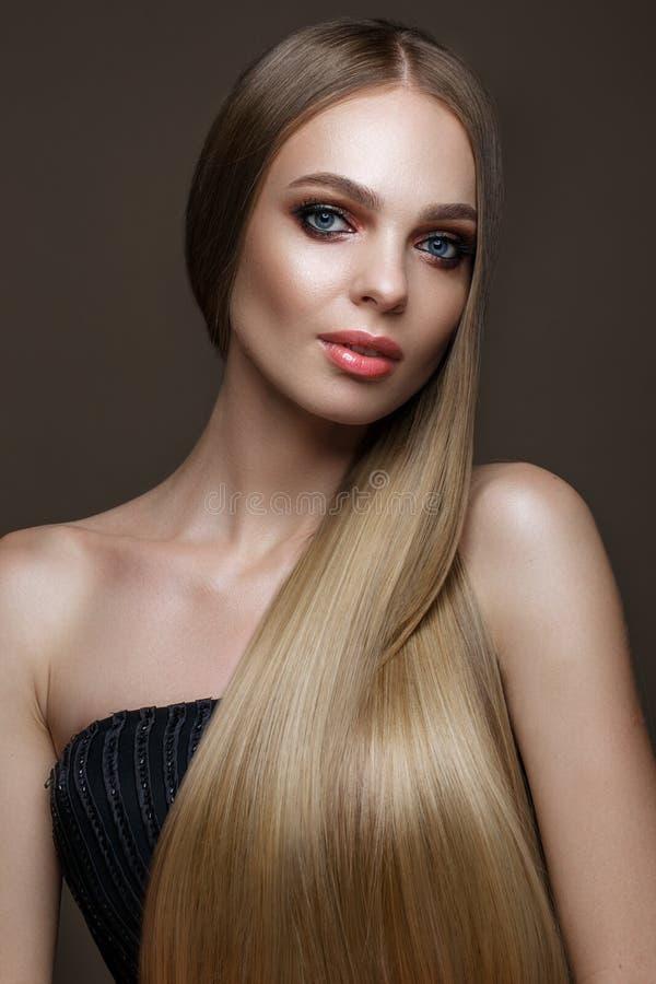 有一片完全光滑的头发、经典构成和红色嘴唇的美丽的白肤金发的女孩 秀丽表面 免版税库存照片