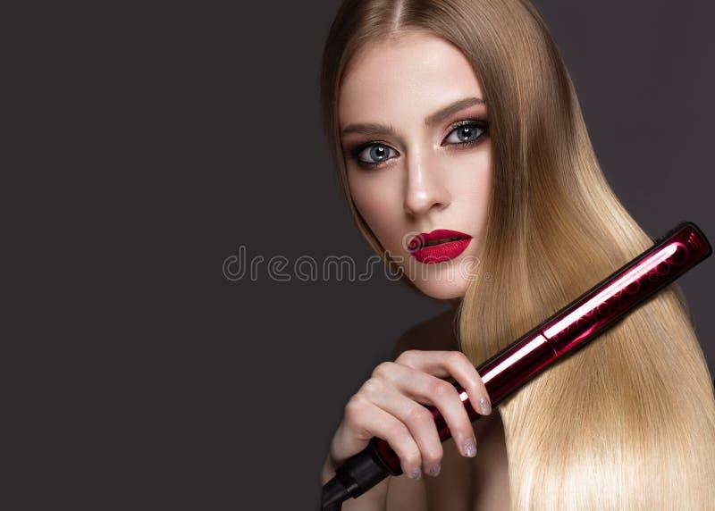 有一片完全光滑的头发,卷曲,经典构成和红色嘴唇的美丽的白肤金发的女孩 秀丽表面 库存图片