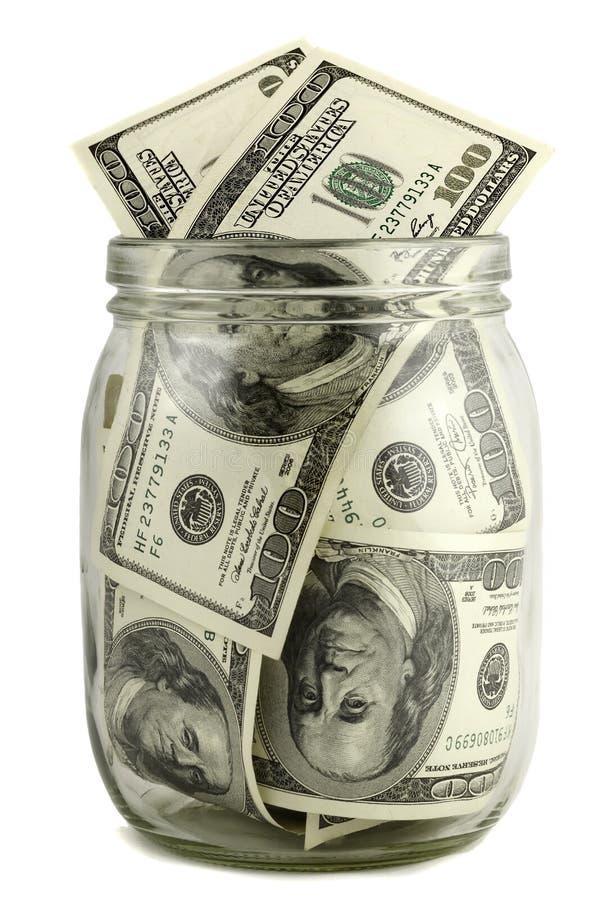 有一百美元笔记的玻璃瓶子 免版税库存图片