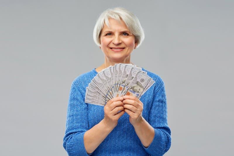 有一百美元金钱钞票的资深妇女 免版税库存图片