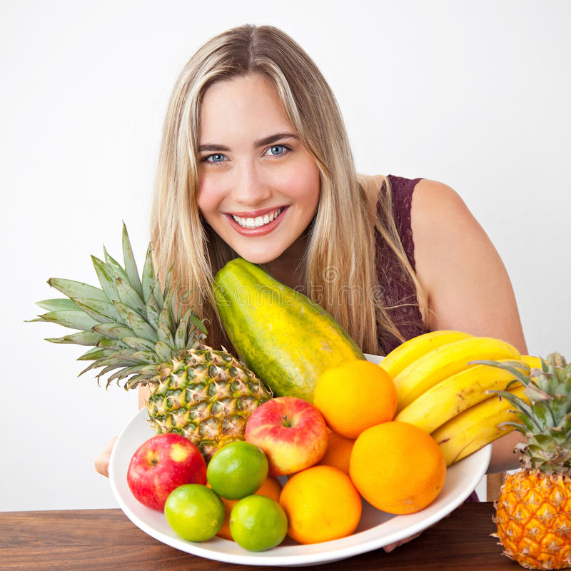 有一碗的年轻健康美丽的妇女新鲜的异乎寻常的果子 图库摄影