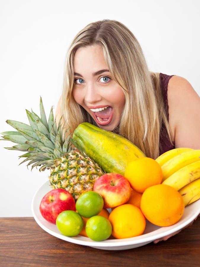 有一碗的年轻健康美丽的妇女新鲜的异乎寻常的果子 免版税库存照片