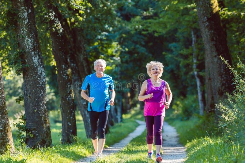 有一种健康生活方式的微笑两个活跃的前辈,当跑步时 库存照片