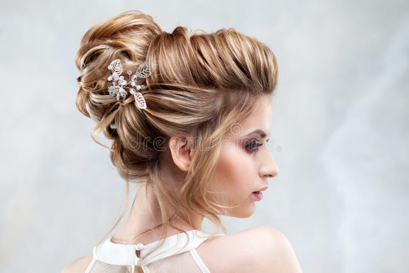 有一种典雅的高发型的年轻美丽的新娘 与辅助部件的婚礼发型在她的头发 免版税库存图片