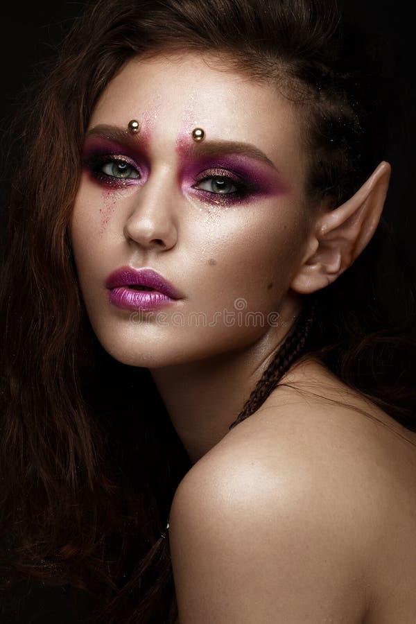 有一种创造性的发型辫子、艺术构成和矮子` s耳朵的深色的女孩 秀丽表面 库存照片