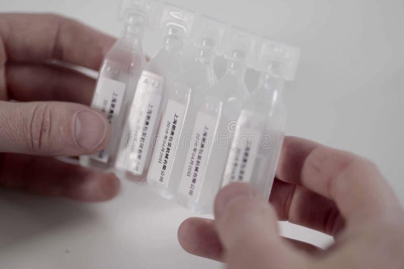 有一种医药物质的塑料细颈瓶从中国在一个人的手上 库存图片