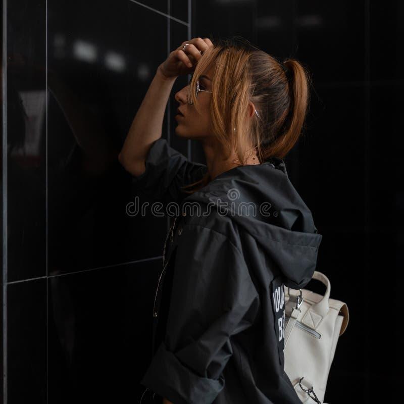 有一种时髦发型的美国年轻女人在葡萄酒玻璃的一件时髦的雨衣与一个时髦的白革背包 免版税图库摄影