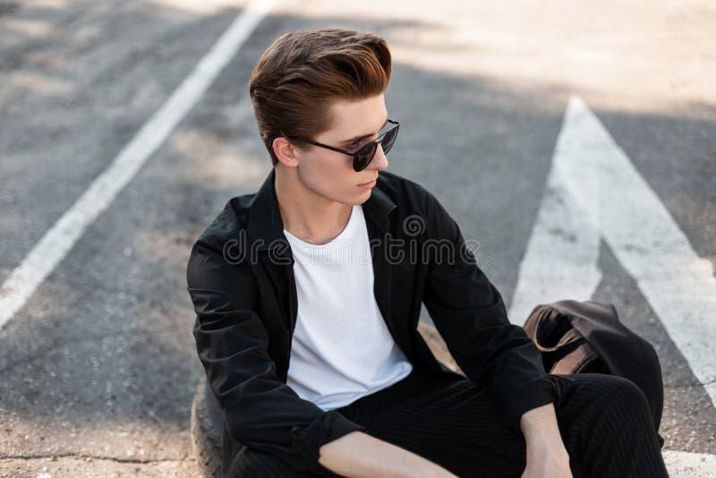 有一种时髦的发型的可爱的年轻人在黑暗的太阳镜的一件黑衬衣休息在沥青的开会在街道 免版税库存图片