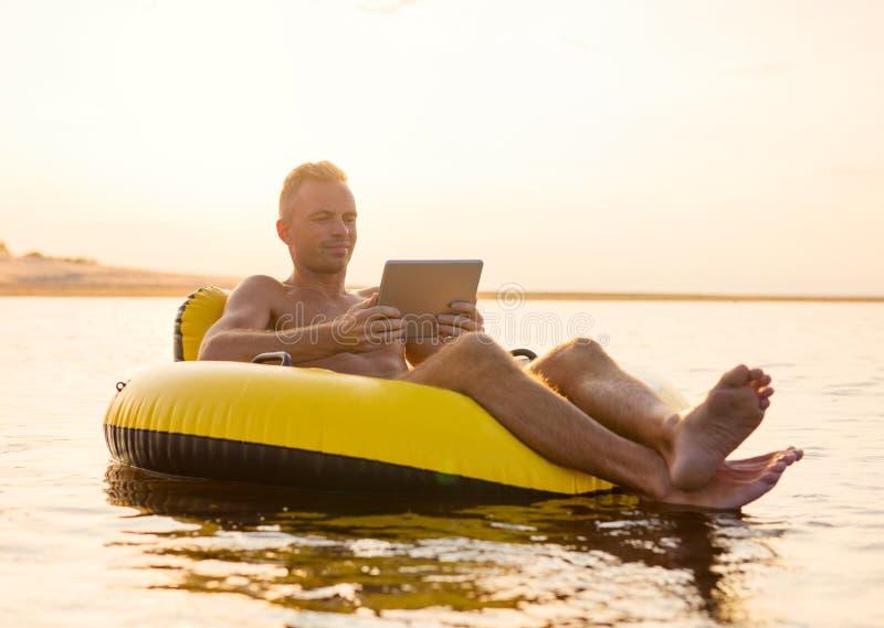 有一种片剂的人在可膨胀的圆环在水中在日落 库存照片