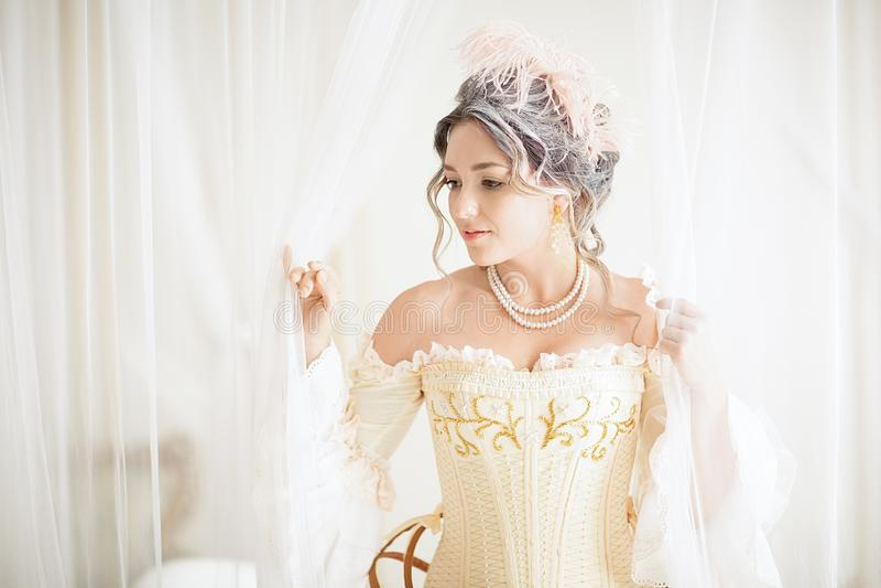有一种美好的豪华洛可可式的发型的一名greyhead妇女在准备好一件白色的礼服洗浴 图库摄影