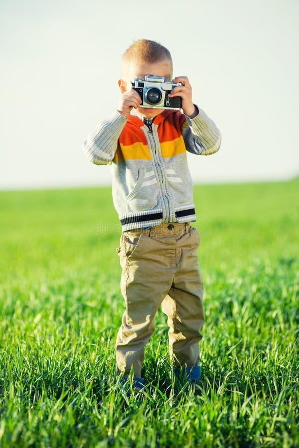 有一老照相机射击的小男孩室外 免版税库存图片
