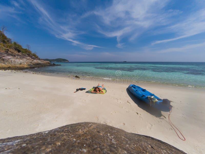 有一艘皮船的妇女在一个孤立海滩在安达曼海,酸值Lipe -独奏旅行 库存图片