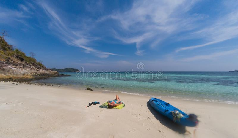 有一艘皮船的妇女在一个孤立海滩在安达曼海,酸值Lipe -独奏旅行 免版税库存照片