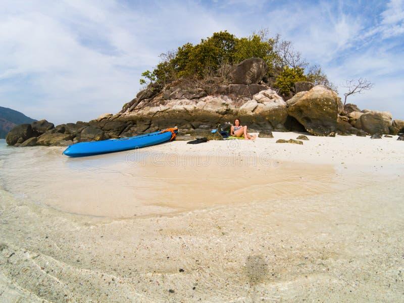 有一艘皮船的妇女在安达曼海独奏旅行的一个孤立海滩 免版税库存照片
