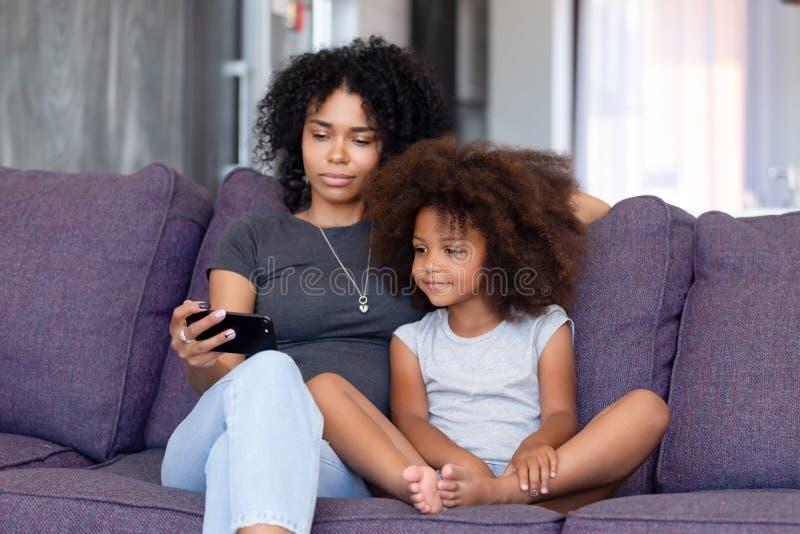 有一起使用电话的女儿的非裔美国人的妇女在家 免版税库存图片
