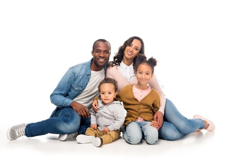 有一起坐和微笑对照相机的两个孩子的愉快的非裔美国人的家庭 免版税库存图片