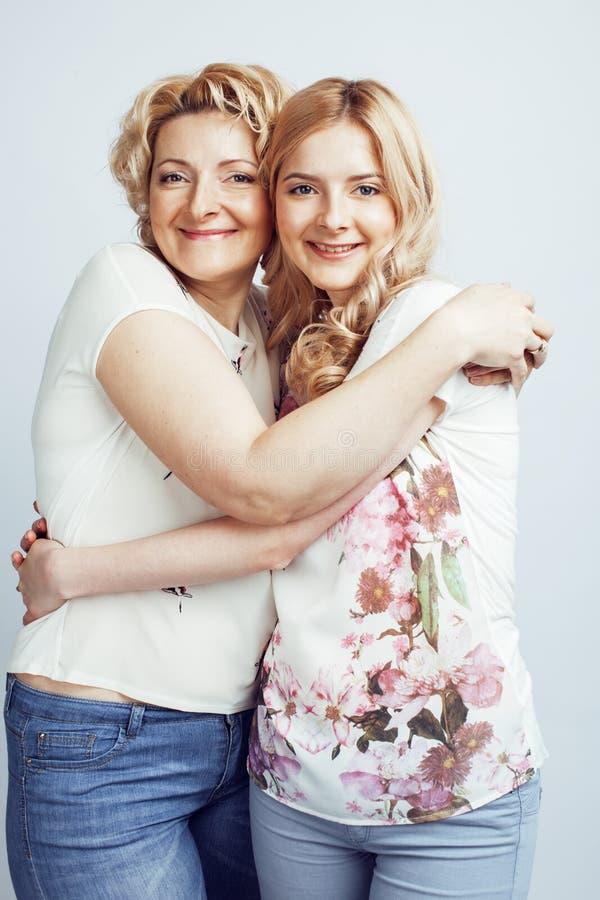 有一起摆在愉快微笑的女儿的母亲隔绝在与copyspace,生活方式人概念的白色背景 免版税图库摄影