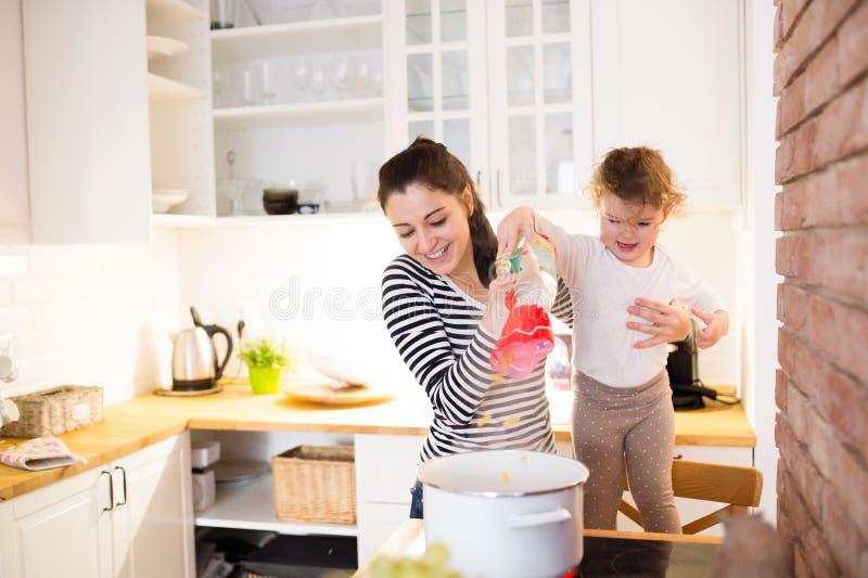 有一起烹调她的女儿的母亲在厨房里 库存照片