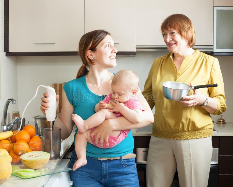 有一起烹调果子纯汁浓汤的孩子的愉快的妇女 库存图片