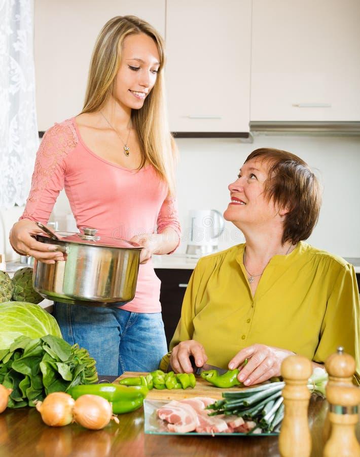 有一起烹调的女儿的愉快的资深妇女 免版税库存照片