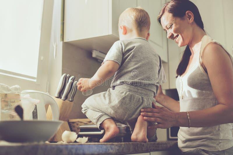 有一起烹调的孩子的母亲 库存图片