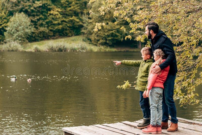 有一起站立和看湖的可爱的小孩的愉快的父亲 免版税图库摄影