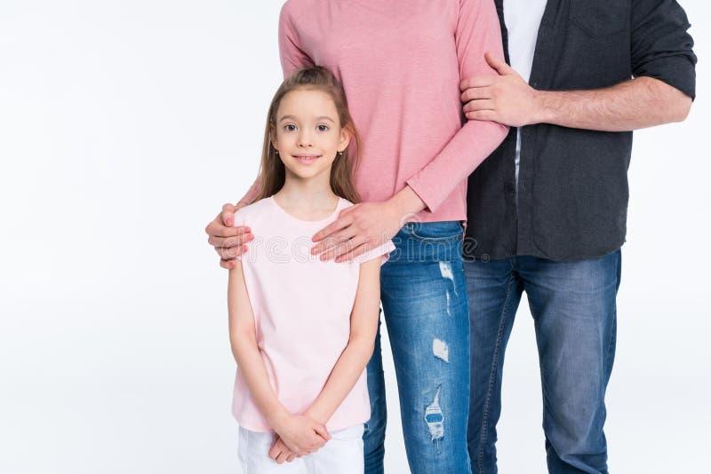 有一起站立在白色的一个孩子的年轻家庭 库存图片