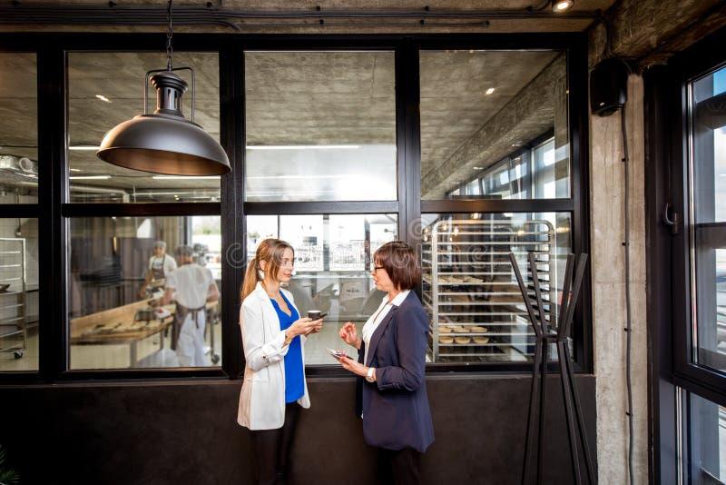 有一起谈话的女商人的面包店办公室 图库摄影