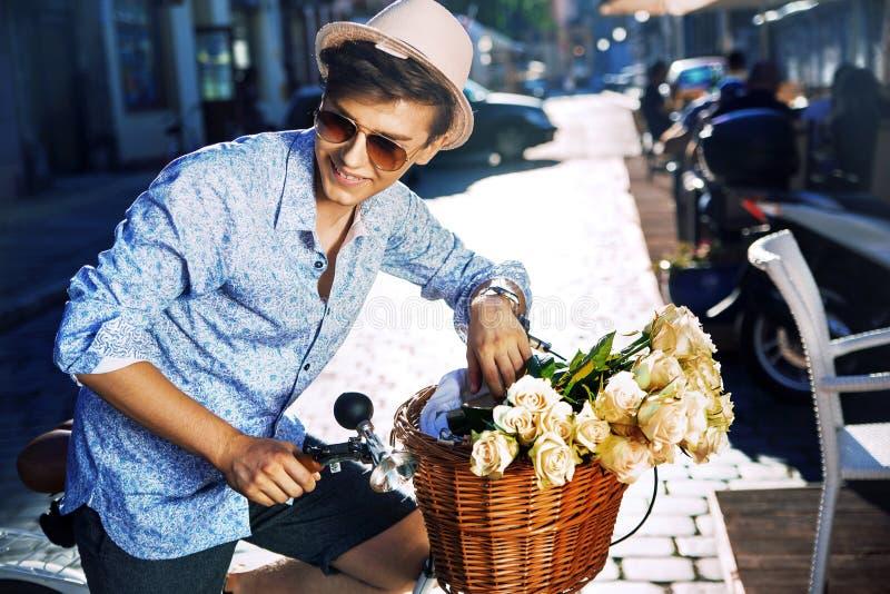 有一辆时髦的自行车的英俊的年轻人 库存照片