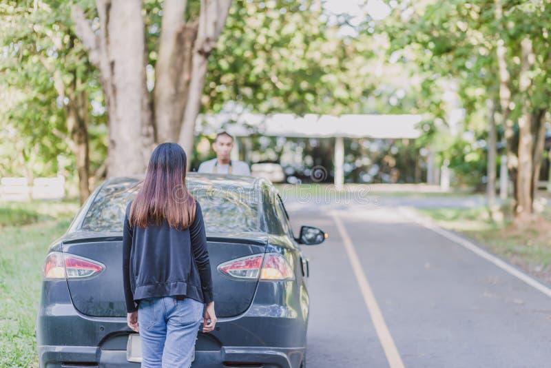有一辆残破的汽车的一名妇女在路 图库摄影