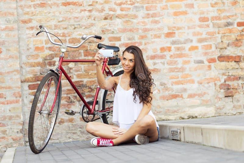 有一辆老红色自行车selfie照片的美丽的妇女他自己-在砖墙前面 免版税库存照片